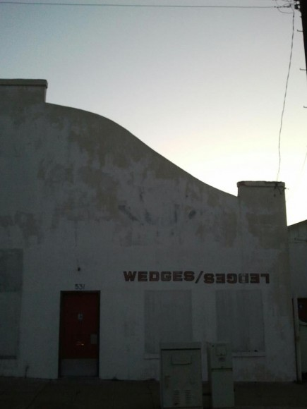 Spanish style white stucco building with a red door and the logo wedges/ledges
